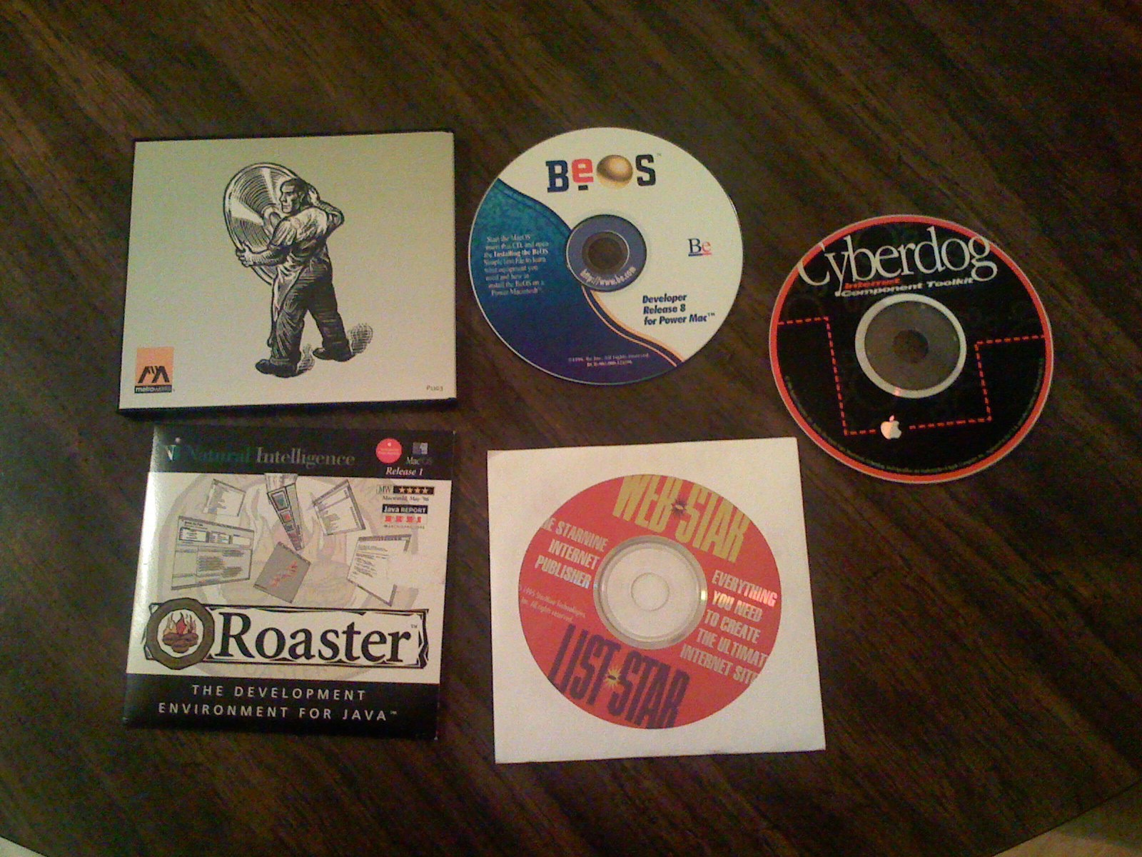 Compact discs and DVDs on a table: CodeWarrior, BeOS, Cyberdog, Roaster, and WebSTAR and ListSTAR.