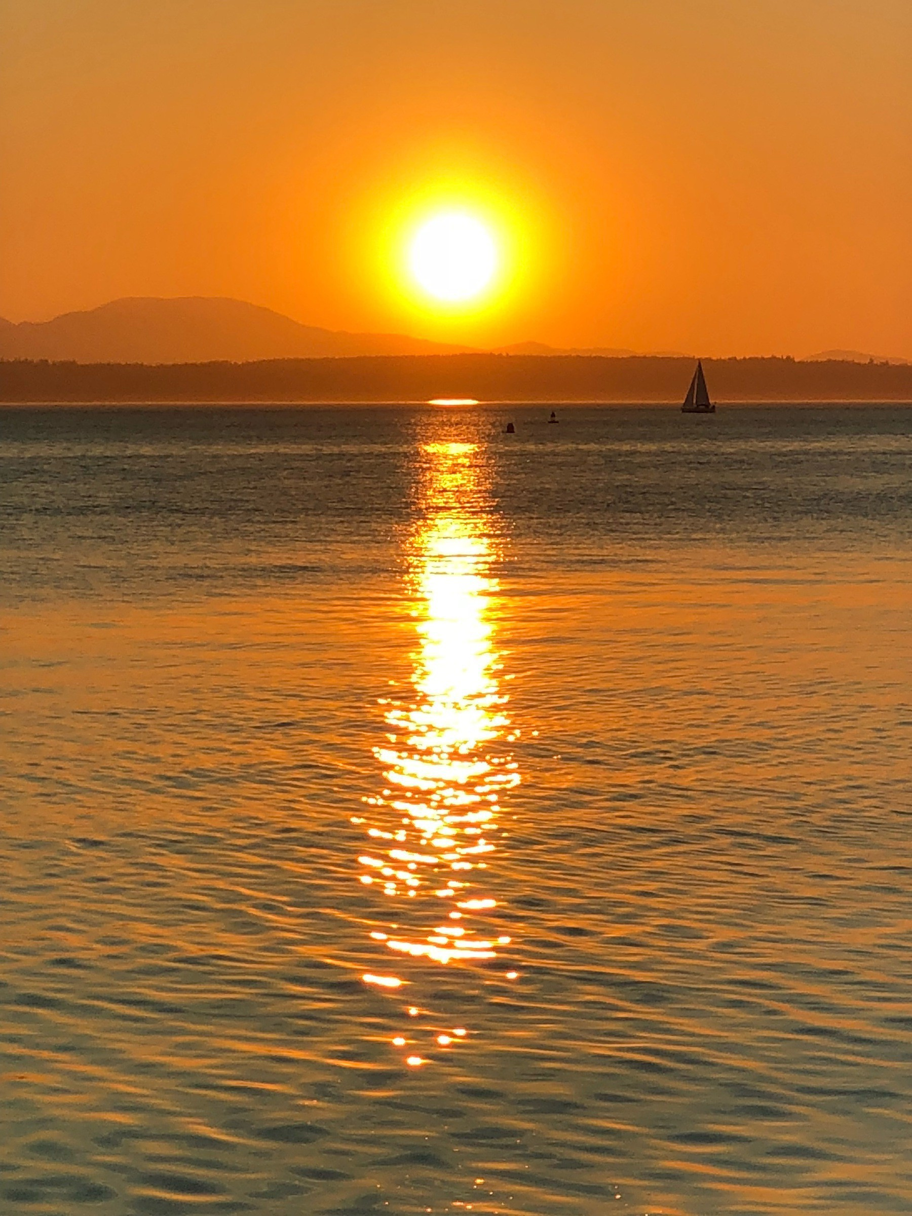 The sun is setting over the Olympics. There are sailboats in Puget Sound.