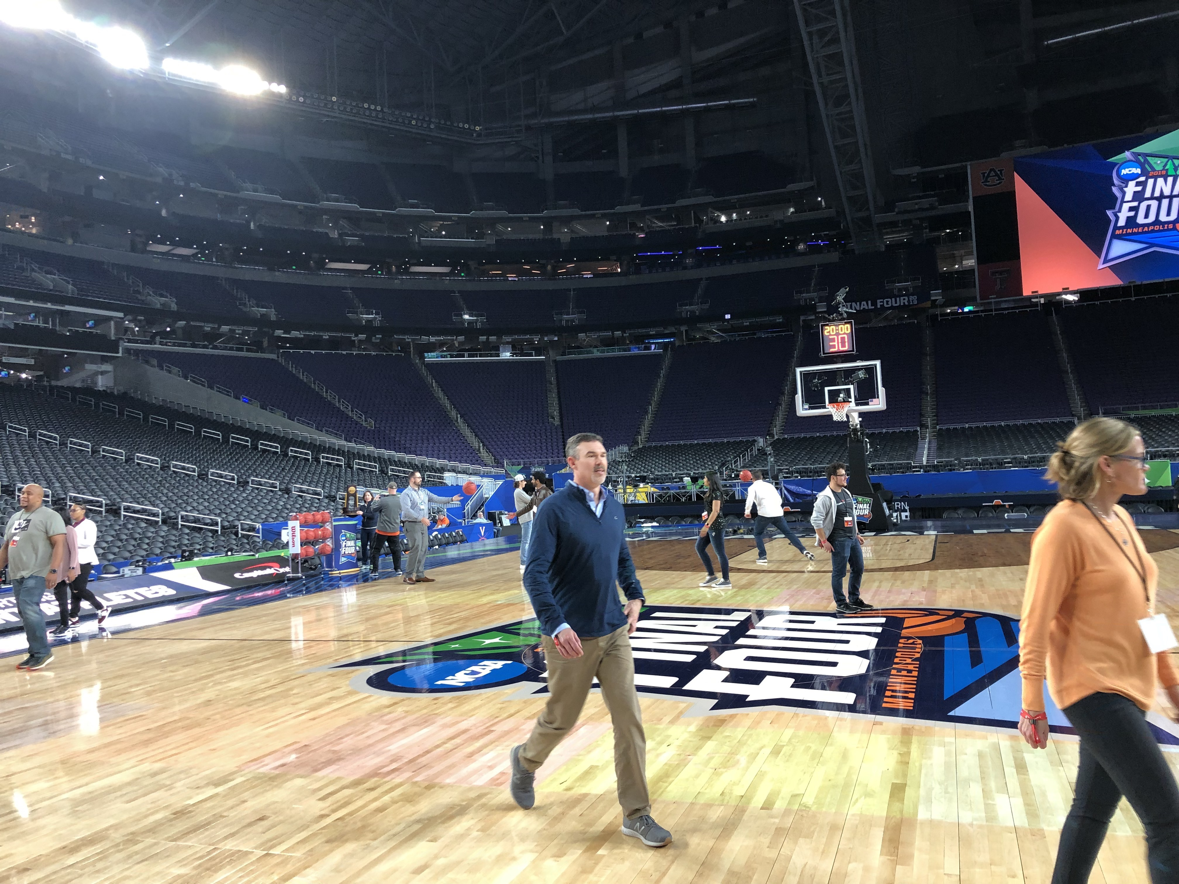Peple on the basketball court the night before the Final Four games. Empty stadium otherwise.