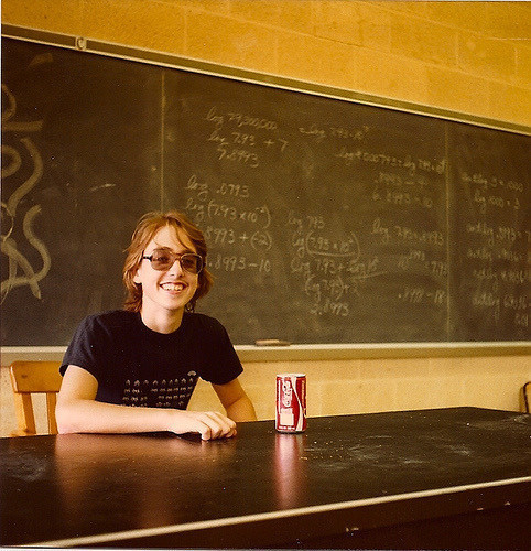 A young Brent sitting at a desk with a Coke can. Brent has long hair; he's wearing slightly tinted glasses and a Space Invaders T-shirt. In the background is a chalkboard with some equations.